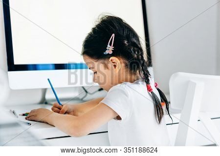 Side View Of Adorable Kid Girl Drawing With Pencils At Home Next To The   Computer. Creative Child S