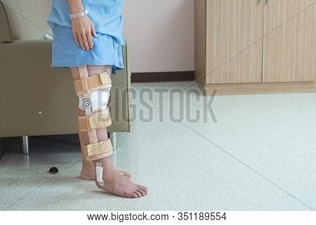 Patient Standing With Support Of Knee Brace And Plaster After Pcl Ligament Knee Surgery In Orthopedi