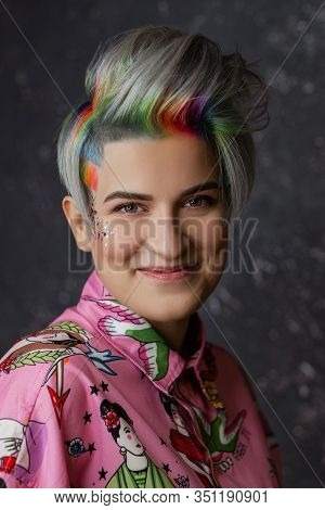 Portrait Of A Young Beautiful Girl In A Pink Shirt On A Gray Background With Dyed Hair. Short Haircu