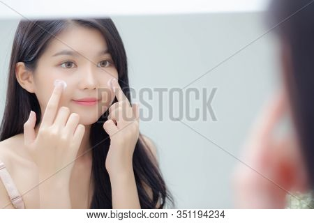 Beautiful Young Asian Woman Smiling Look At Mirror Of Checking Face With Skin Care And Cosmetic For
