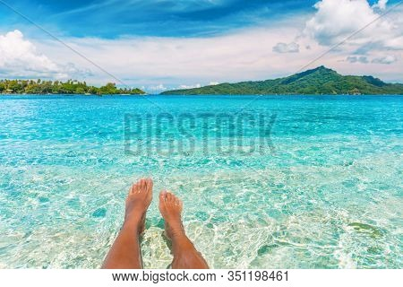 Relax feet selfie woman lying in turquoise crystalline blue water on French Polynesia motu beach vacation summer. Woman relaxing on tropical travel destination swimming sun tanning.