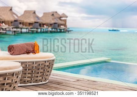 Luxury Bora Bora overwater bungalow villas high end hotel in Tahiti, French Polyneisa. Ocean view summer travel destination resort background, sun lounger with towel , sunscreen and sunglasses.