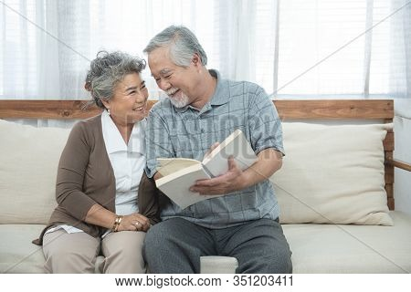 Elderly Senior Asian Couple Sitting On Sofa Reading Book Together At Home.retirement Grandmother And