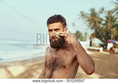 Handsome Man With Beard, Sunbathing With Sunscreen Lotion Body In Summer. Male Fitness Model Tanning