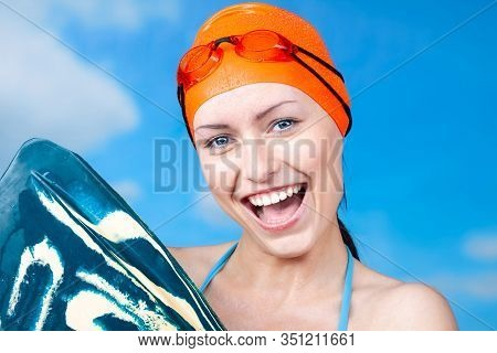 A Winner -  Young Sexy Female Swimmer In An Orange Swimming Cap And Swimming Glasses, Smiling Openly