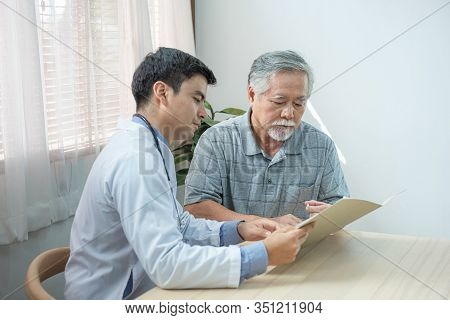 Profile View Of Caucasian Cardiologist Consulting Doctor With His Senior Elder Asian Patient With He