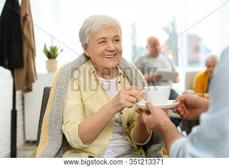 Care Worker Giving Drink To Elderly Woman In Geriatric Hospice
