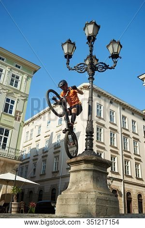 Young Man Is Performing Extremal Trick With His Bmx Bike, Keeping Balance On Back Wheel On A Pillar