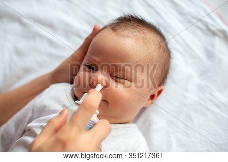 Woman Using Nasal Spray For Baby. Nasal Congestion