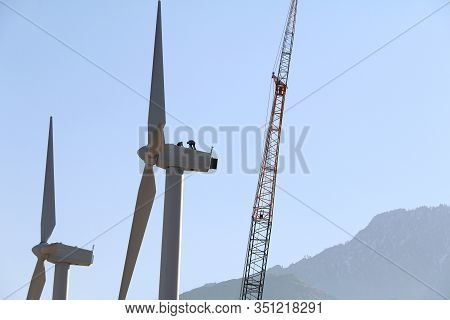 2 Workers On Top Of Wind Turbine In A Mountain Desert Area