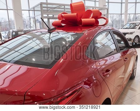 New Red Car With Red Gift Ribbon Atop In The Car Dealer Showroom Back View