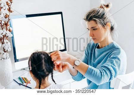 Pretty Young Woman With Daughter Sitting At Home And Working. Young Mother With Toddler Child Workin