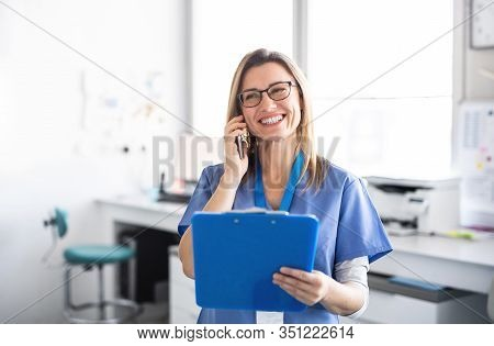 A Portrait Of Dental Assistant In Modern Dental Surgery, Using Smartphone.