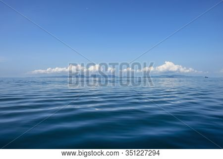 Blue Ocean With Waves And Clear Blue Sky Blue Water Surface. Travel Destination And Nature Environme