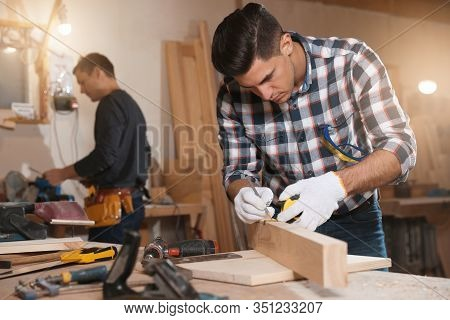 Professional Carpenter And Colleague Working With Wooden Plank In Workshop
