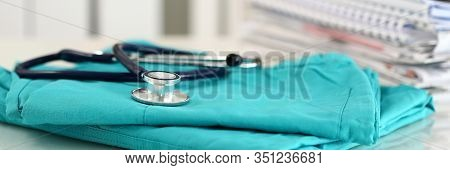 Medical Stethoscope Lying On Green Doctor Uniform Closeup. Medical Tools And Instruments Shop, Thera