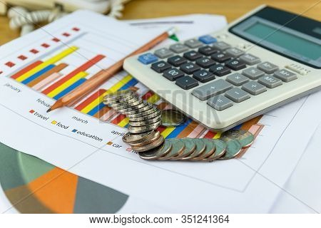The Stack Of Coin With Business Paper Graphs And Pencil With Charts Report, Calculator, Concept Of C