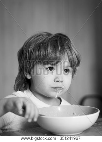 Happy Child. The Child In The Kitchen At The Table Eating. Little Baby Are Eating. Good Morning In H