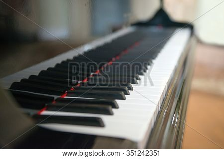 Piano Side View With Keys Lost In The Light. Piano Keys Side View With Shallow Depth Of Field. Piano