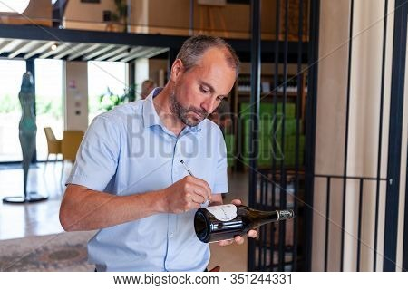 France Chablis 2019-06-21 Man Winemaker Signs Label Of Wine Bottle