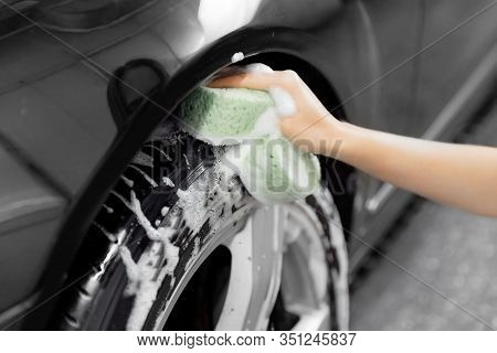 Service Car Wash Express. Girl Worker Clean Tire And Rubber Wheel With Sponge