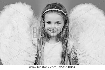 Wonderful Blonde Little Girl In The Image Of An Angel With White Wings. Angel Kid With Blonde Curly