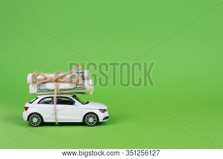 Earn Cash With Your Car Concept. Side Profile Full Photo Picture Of Small White Car With Rolls Piles