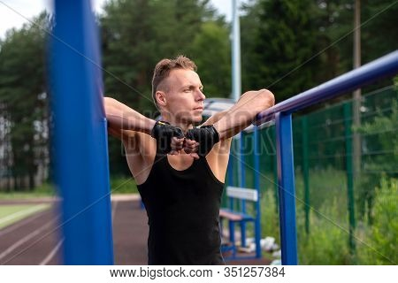 A Man Is Pushing Up From Parallel Bars