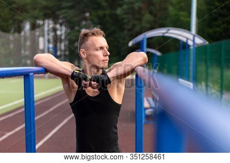 A Muscular Man Stands Leaning On Parallel Bars, With A Bare Torso.
