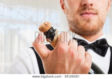 Portrait of a waiter holding a champagne bottle