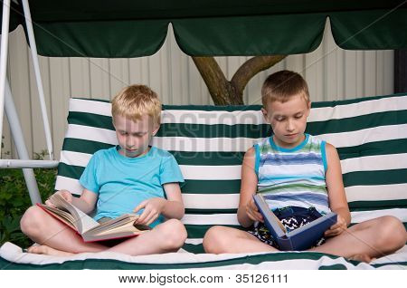 8-year Schoolboy And 6-year Preschooler Reading Books