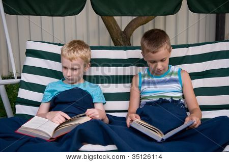 8-year Old Schoolboy And 6-year Old Preschooler Reading Books