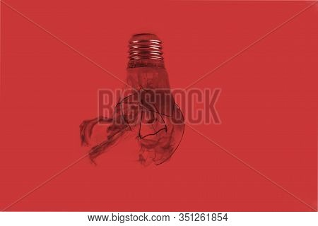 One Broken Light Bulb On A Red Background With Smoke. Overdue Idea Concept. World Not Electric. Eart
