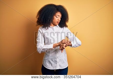 Young beautiful african american elegant woman with afro hair standing over yellow background Checking the time on wrist watch, relaxed and confident