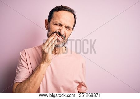 Middle age hoary man wearing casual t-shirt standing over isolated pink background touching mouth with hand with painful expression because of toothache or dental illness on teeth. Dentist