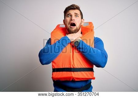 Young blond tourist man with beard and blue eyes wearing lifejacket over white background shouting and suffocate because painful strangle. Health problem. Asphyxiate and suicide concept.