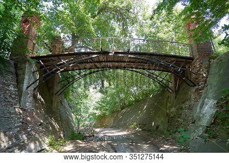 An Old, Dangerous Bridge In Disrepair For Pedestrians In A Park.