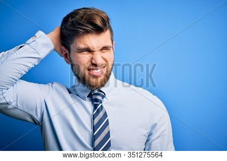 Young blond businessman with beard and blue eyes wearing elegant shirt and tie standing confuse and wonder about question. Uncertain with doubt, thinking with hand on head. Pensive concept.