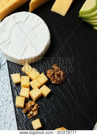 Pieces Of Cheese On A Dark Background. Cheeseboard. Sliced ​​apple And Nuts On The Board. Hard Chees