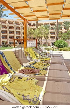 Hurghada / Egypt. 30 July 2018:  Empty Deck Chairs With Towels On Tropical Resort Beach. Chaise Long