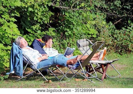 Lodz / Poland. 18 July 2019: Two Women Pensioners Rest In City Park. Elderly Women Enjoy Vacation In