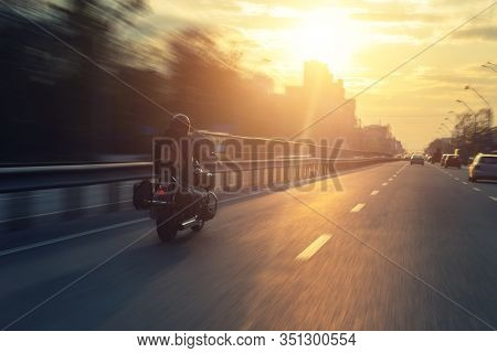 Silhouette Of Biker Riding Black Chopper Motorcycle On City Street Highway Road And Sunset Bright Dr