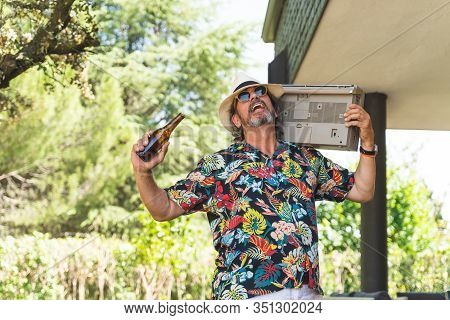 Retired Man With Beer Listening Music And Dancing. Pensioner Man Having Fun And Listening Music From