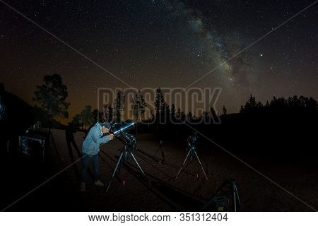 Young Man Observes Starry Sky Through A Telescope. Mountains, Surrouded By Pine Tree Forest In The B