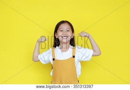 Strong Asian Little Kid Girl Raising Hands Up And Smiling. Portrait Of Happy Child In Dungarees Isol