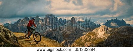 Cycling outdoor adventure. Man cycling on electric bike, rides mountain trail. Man riding on bike in Dolomites mountains landscape. Cycling e-mtb enduro trail track. Outdoor sport activity.