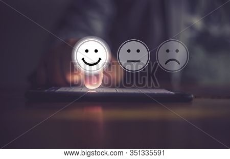 Businessman Pressing Face Emoticon On Virtual Touch Screen At Smartphone .customer Service Evaluatio