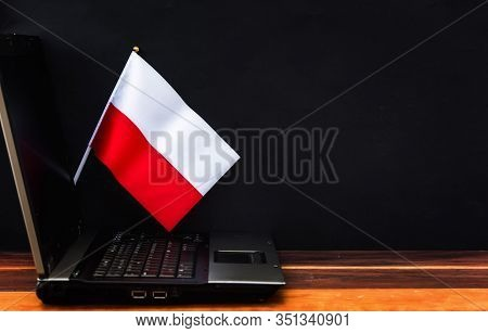 Flag Of Poland , Computer, Laptop On Table And Dark Background