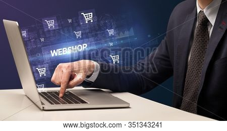 Businessman working on laptop with WEBSHOP inscription, online shopping concept