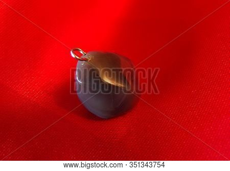 Stone Amethyst Pendant On A Red Cloth At A Jewelry Store. Pendant And Necklace Made Of Stone. Jewelr